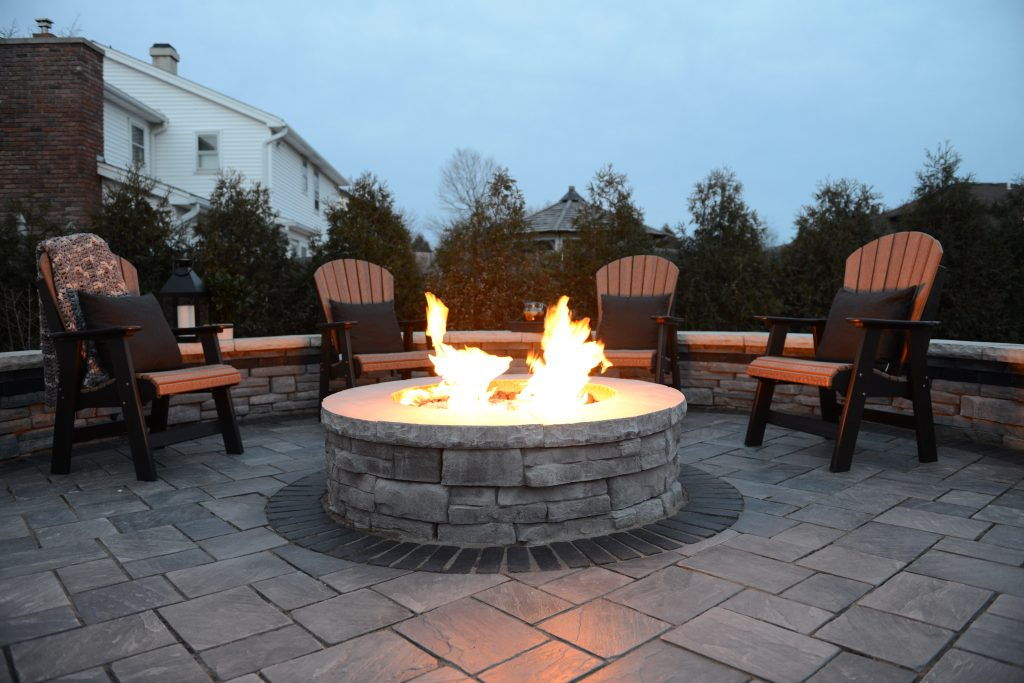 Rich Textures Define this Sunken Fire Pit Patio by Pace Landscaping & Ice Rinks in West Seneca, NY